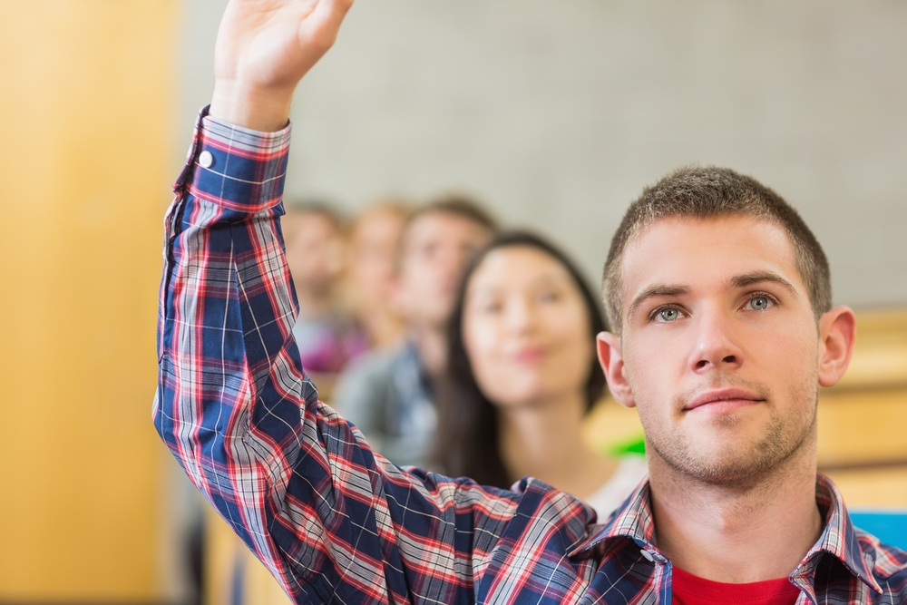 Leading curriculum change amid a changing job market. Close-up of a young male student raising hand by others in a row at the classroom.jpeg