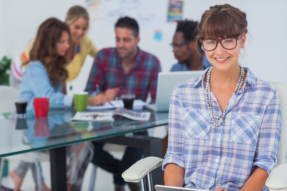 Employment skills and student employability - Cheerful designer holding a tablet pc with colleagues working behind.jpeg